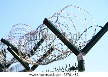 Barbed wire against a blue sky - stock photo
