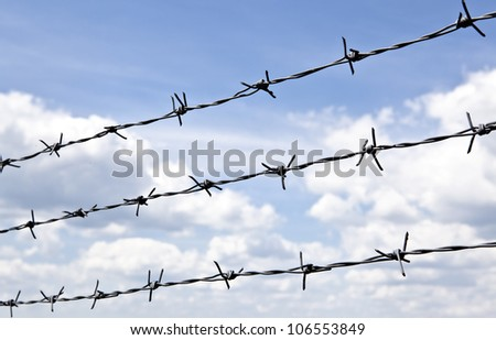 Barbed wire against blue sky with clouds - stock photo