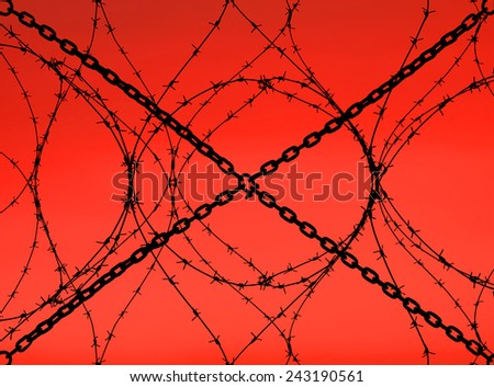 Barbed wire and chains with bloody sunset in the background - stock photo