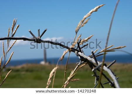 Barbed wire detail at Pointe-du-Hoc memorial, Normandy, France, where the Rangers climbed the cliffs during D-Day, WWII - stock photo