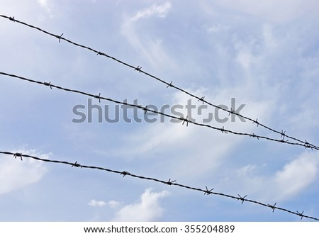 barbed wire fence against a blue sky