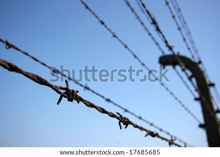 Barbed wire fence against clear blue sky