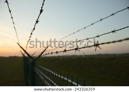 Barbed wire fence against clear blue sky - stock photo