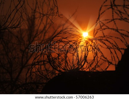 Barbed wire fence and Light of Hope. - stock photo