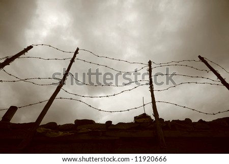 barbed wire fence and wall - stock photo