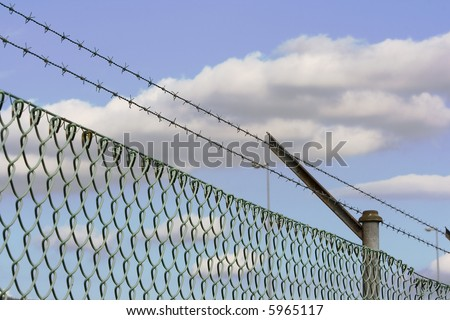 barbed wire fence as a security system - stock photo