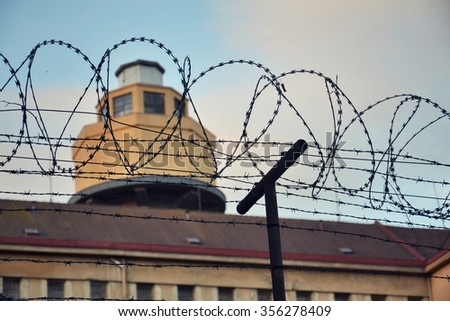 Barbed wire fence attached around prison walls - stock photo