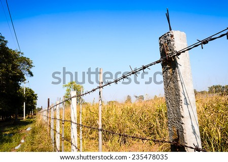 barbed wire fence blocking the meadow with blue sky