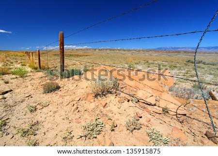 Barbed wire fence divides the vast open spaces of Wyoming - stock photo