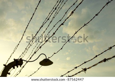 Barbed wire fence in Auschwitz II-Birkenau Concentration Camp in Poland near Krakow. - stock photo