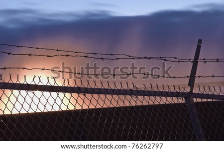Barbed-wire fence in front of spectacular sunset. - stock photo