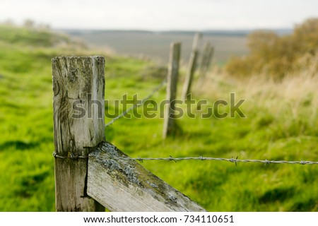 Barbed wire fence in rural Northumberland against a blurred countryside background.