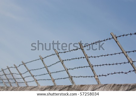 Barbed wire fence on concrete wall with blue sky background - stock photo