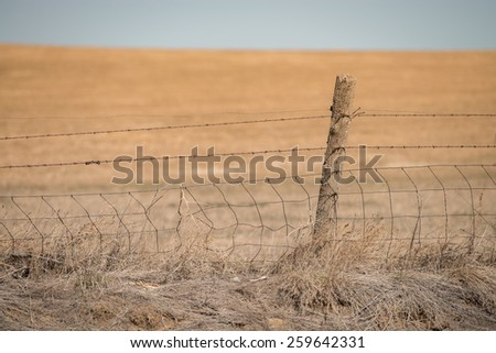 Barbed Wire Fence & Post on the Plains - stock photo