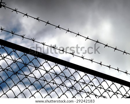 Barbed wire fence with dark clouds in background - imprisonment concept - stock photo