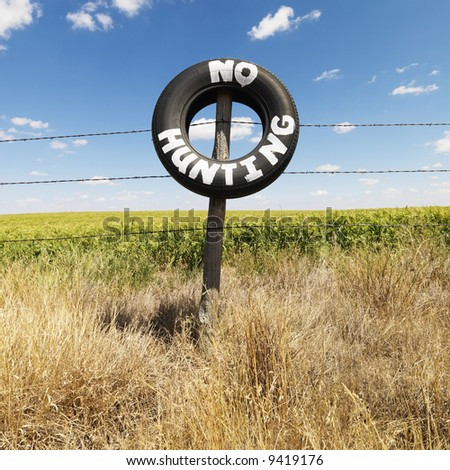 Barbed wire fence with tire reading No Hunting in front of agricultural field. - stock photo