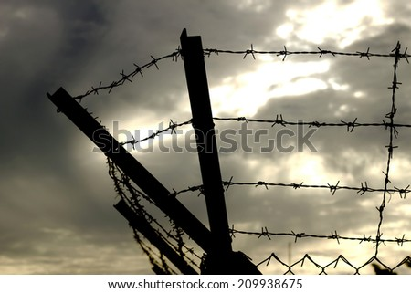 Barbed wire on dark fence. Monochrome silhouette photo  - stock photo