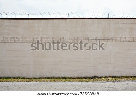barbed wire on wall - stock photo