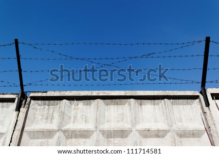 Barbed wire over old concrete wall - stock photo