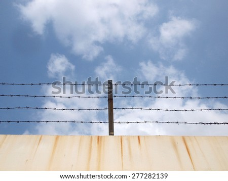 Barbed wire over old concrete wall