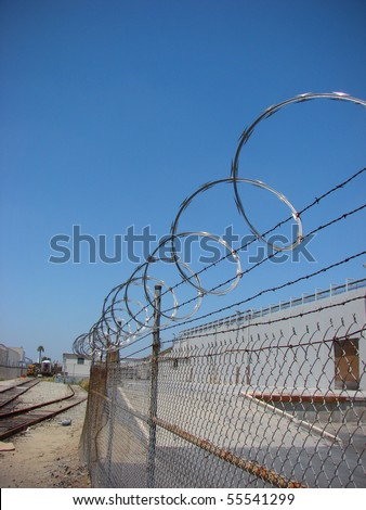 barbed wire razor fence with blue sky and industrial building