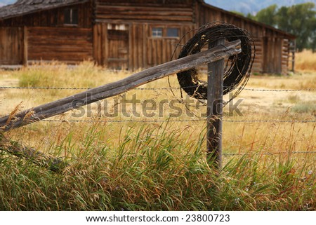 Barbed-wire roll hung on fence near vintage barn - stock photo