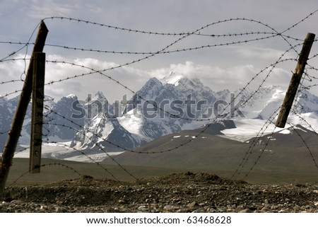 barbed wire wall in the mountains - stock photo