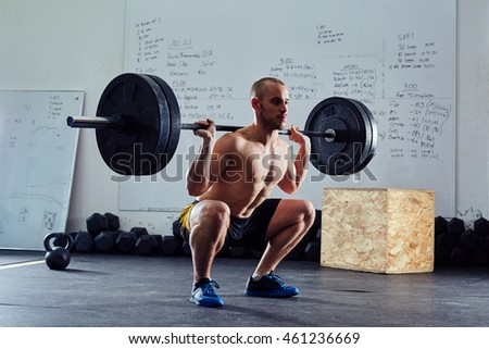 Barbell squat exercise - athletic man during weightlifting workout at the gym