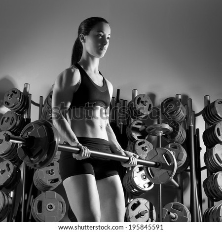 Barbell woman workout fitness club at weightlifting gym - stock photo