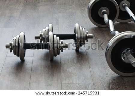 barbells and dumbbells perpendicular to each other - stock photo