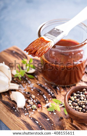 Barbeque sauce with a basting brush in a jar - stock photo
