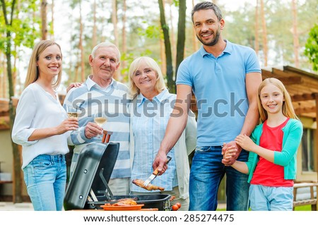 Barbeque time. Happy family of five people barbecuing meat on grill and looking at camera - stock photo