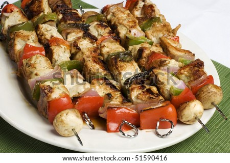 Barbequed kebabs on white plate with green background - stock photo