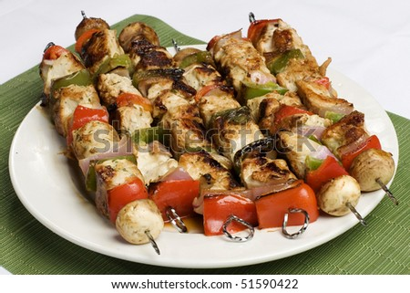 Barbequed kebabs on white plate with green place mat - stock photo