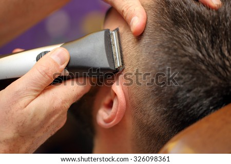 Barber cutting and modeling hair by electric trimmer