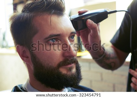 barber cutting hair with electric clipper in a barber shop - stock photo