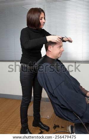 Barber cutting hair with scissors and comb, using cosmetic in spray, client is a  caucasian man - stock photo