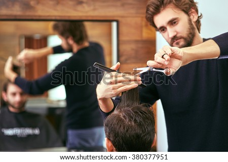 barber cutting hair with scissors. back view of man in barber shop.  - stock photo