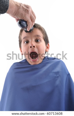Barber cutting little child's hair with scissor over white background - stock photo