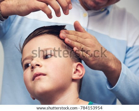 Barber Is Making A Hairstyle With Hair Gel To A Boy In Barbershop.