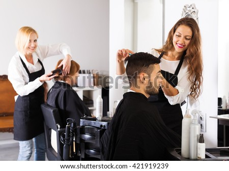 Barber makes the haircut for young man in the barbershop