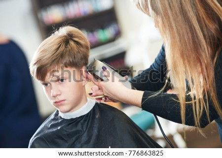 Barber or hair stylist at work. female hairdresser cutting child hair