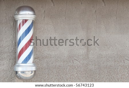 Barber pole on stone wall - stock photo