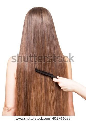 Barber's hand combing her long straight hair isolated on white background.