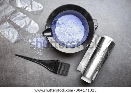Barber set with hair dye, foil and brush on grey background - stock photo