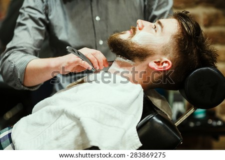 Barber shaving a bearded man in a barber shop, close-up - stock photo