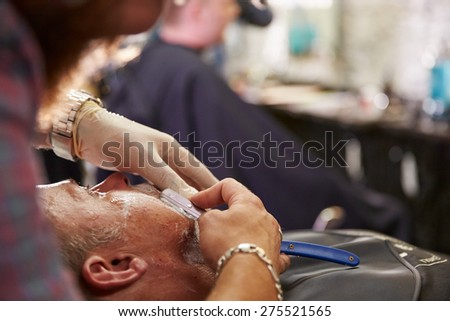Barber Shaving Client With Cut Throat Razor - stock photo