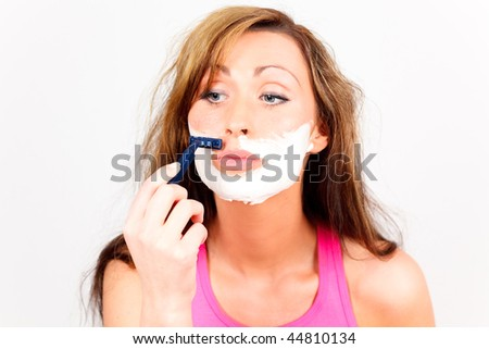 Barber shaving facial female looking in mirror - stock photo