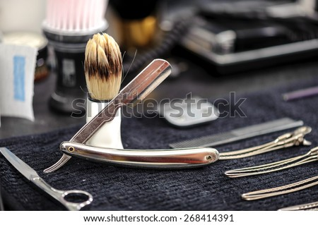 Barber tools. Close-up of elegant old brush with white handle for shaving and range of old-fashioned straight razors on a barbers table - stock photo