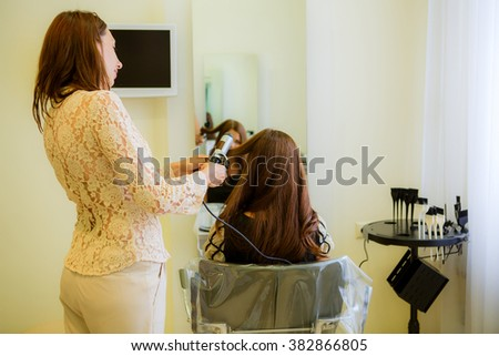 Barber twists curls beautiful girl in a beauty salon - stock photo